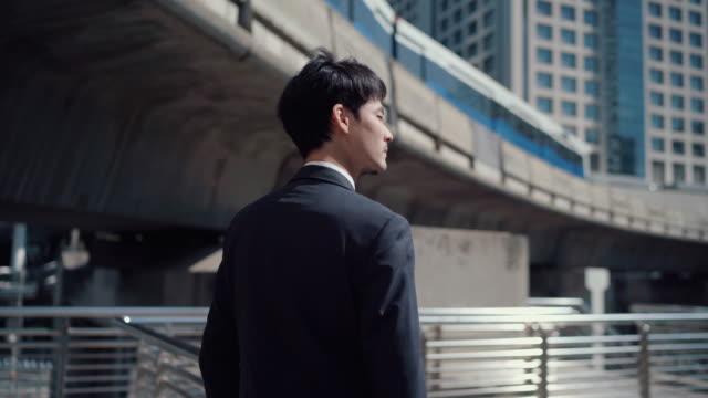街の通りを歩く若いビジネスマン - 希望点の映像素材/bロール