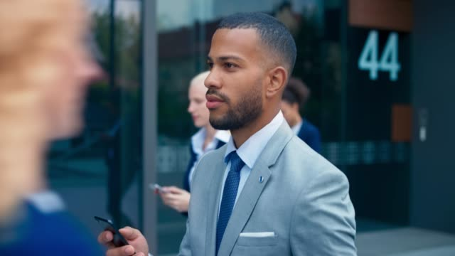 SLO MO TS Young businessman walking while scrolling his smartphone Slow motion medium tracking shot of a young biracial business man in a nice grey suit walking outside the modern business building while scrolling his smartphone. Shot in Slovenia. black people stock videos & royalty-free footage