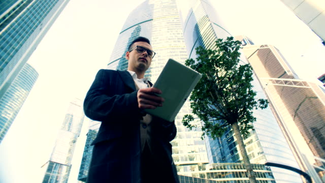 vidéos et rushes de jeune homme d'affaires marche, tapant sur une tablette, vue inférieure. - vue en contre plongée