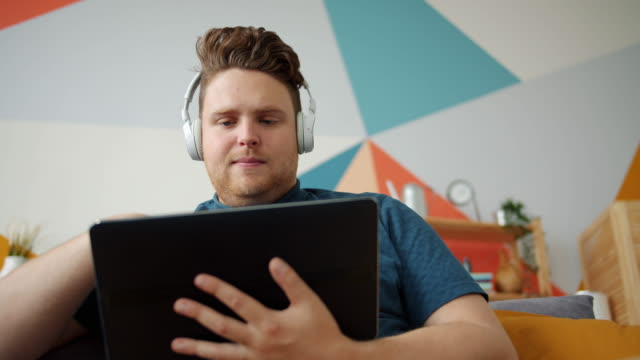 young businessman wearing headphones touching tablet screen in apartment - cuffie wireless video stock e b–roll