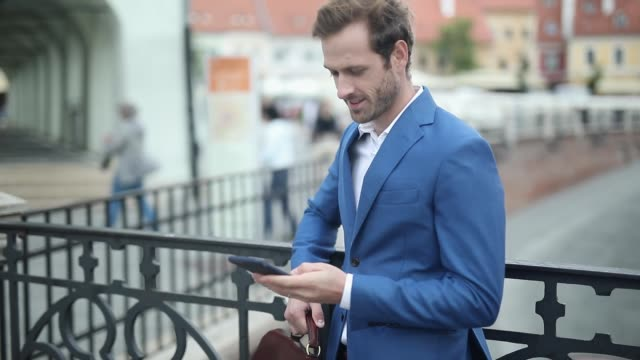 vídeos de stock e filmes b-roll de young businessman wearing navy suit resting on railing holding a briefcase pulling out his phone from pocket - puxar