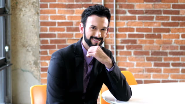 Young businessman wearing suit smiling at camera