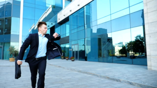 Young businessman with briefcase runs and looks at his watch. Confident guy late for meeting. Successful man in suit runs near modern building. Handsome man in hurry to appointment. Slow motion