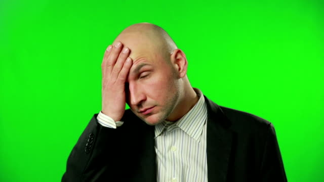 Young businessman with headache against a green screen video