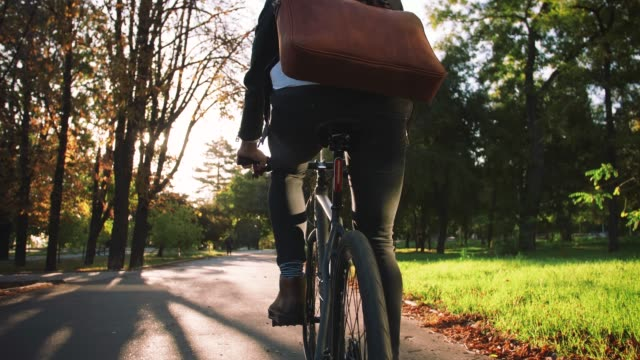 Young businessman with leather bag riding bicycle to city park, slow motion, back view