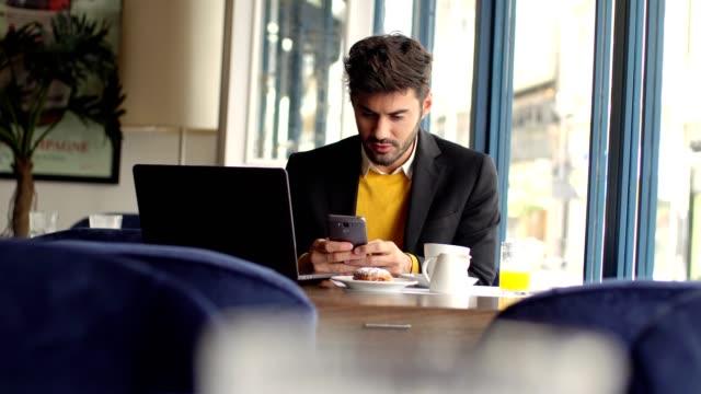 ung affärsman som arbetar på café - skicka datormeddelande bildbanksvideor och videomaterial från bakom kulisserna