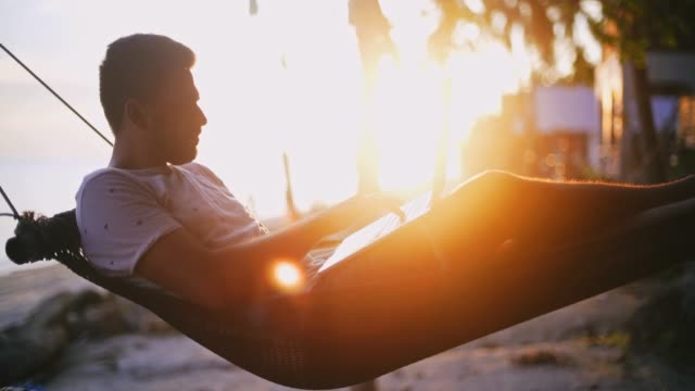 Young businessman working on his computer on vacation on a tropical island in the rays of the setting sun.