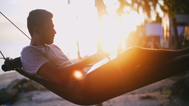 stockvideo's en b-roll-footage met young zakenman werkt aan zijn computer op vakantie op een tropisch eiland in de stralen van de ondergaande zon. - oost azië