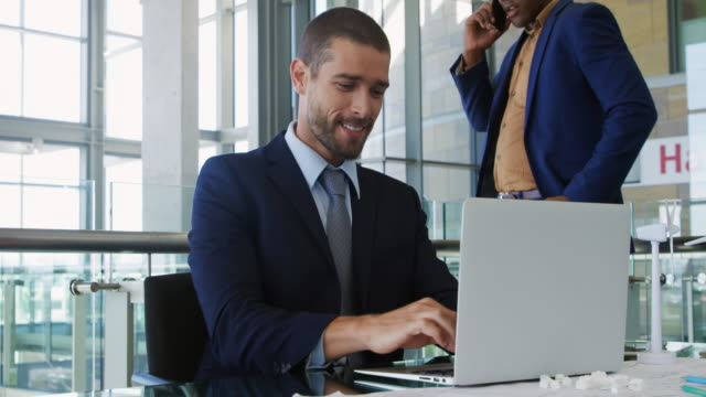 Young businessmen working in a modern office Front view close up of a young Caucasian businessman sitting at a desk using a laptop computer and talking and smiling in a modern office, while his young African American male colleague stands talking on a smartphone in the background telephone receiver stock videos & royalty-free footage