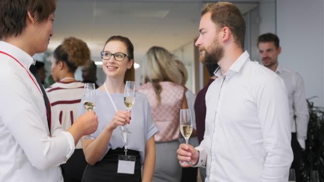 vídeos de stock, filmes e b-roll de jovens empresários brindando com champanhe na festa - festas no escritório