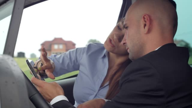 Young businesspeople work with tablet in car video