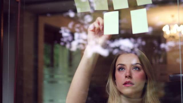 vídeos y material grabado en eventos de stock de joven empresaria lluvia de ideas con notas en una pared de vidrio en una oficina - pegajoso