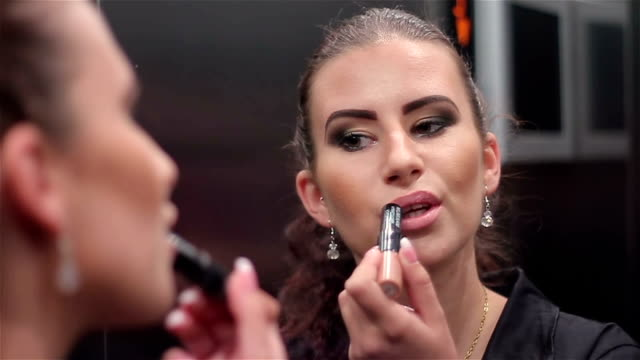 Young businesswoman corrects her makeup in the elevator,close up video
