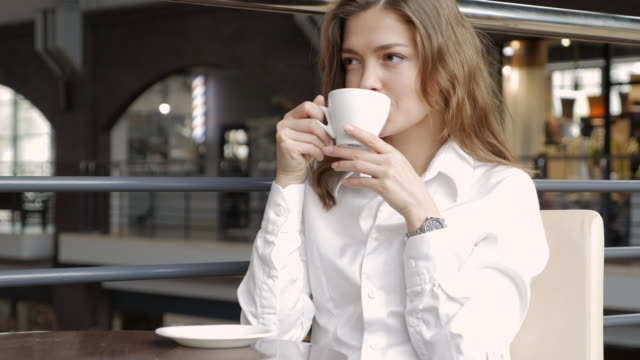 Young businesswoman enjoying coffee and looking around while sitting in the cafe video