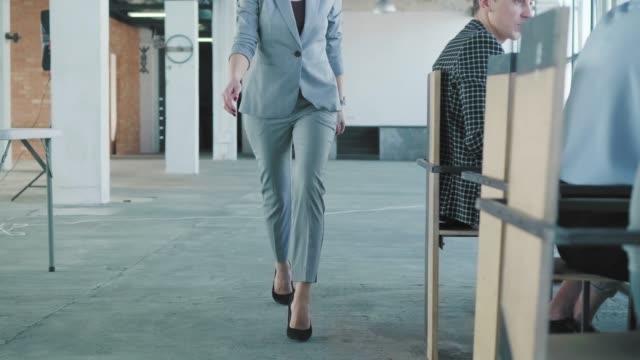 Eine junge Geschäftsfrau betritt das Büro und geht an den Tisch, wo ihre Kollegen warten. Sie applaudiert den Mitarbeitern und beginnt ein Met-ap. Creative Office Interieur. Co-Working Startup Team. Arbeitnehmer – Video