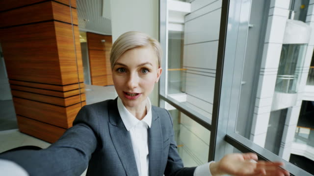 pov of young businesswoman in suit having online video chat using smartphone camera and talking to his colleagues in modern office - woman chat video mobile phone video stock e b–roll