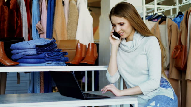 young businesswoman is working with laptop and talking on mobile phone in her shop. clothes and customer in background. small business concept. - owner laptop smartphone video stock e b–roll