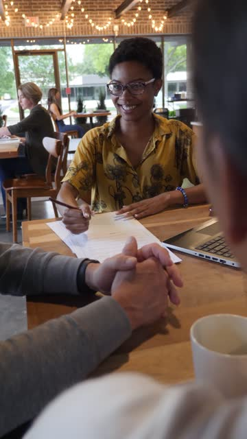young businesswoman leads meeting with colleagues in coffee shop - vertical format video stock videos and b-roll footage