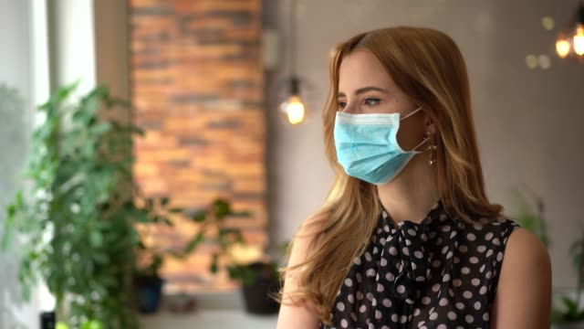 Young businesswoman looking at camera Businesswoman with face mask in the office during COVID-19 pandemic occupational safety and health stock videos & royalty-free footage