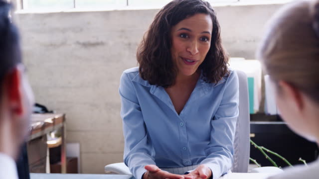 Young businesswoman meeting with a couple in her office Young businesswoman meeting with a couple in her office financial occupation stock videos & royalty-free footage