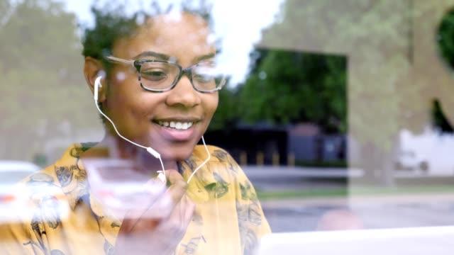 genç iş kadını, kahve dükkanında iken video konferansına katılır - virtual meeting stok videoları ve detay görüntü çekimi