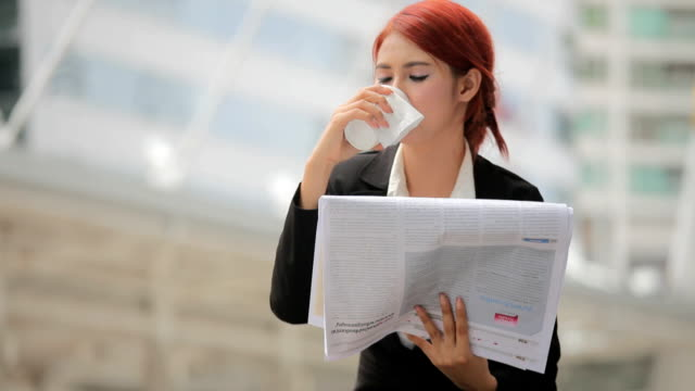 Young businesswoman reading newspaper and coffee video