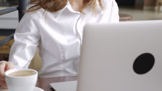 Young businesswoman sitting in the cafe and working on laptop video