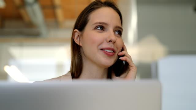stockvideo's en b-roll-footage met jonge zakenvrouw praten op mobiele telefoon op het werk - gewone snelheid
