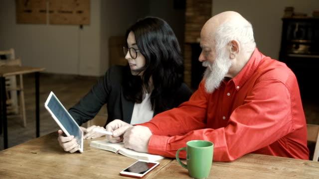 vídeos de stock e filmes b-roll de young businesswoman talks with mature man holding tablet in hands - senior business woman tablet