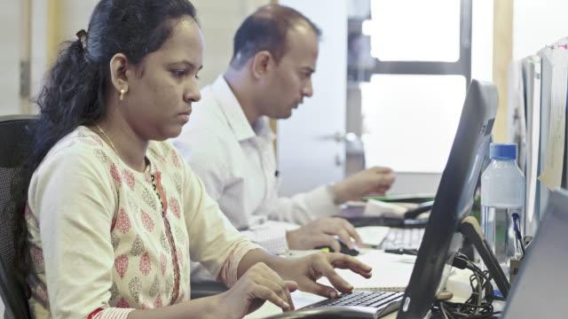ofiste bilgisayar kullanan genç iş kadını - hindistan stok videoları ve detay görüntü çekimi