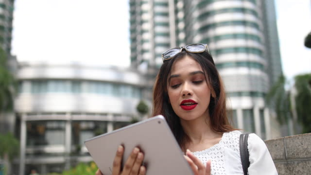 young businesswoman using digital tablet on her way to work - etnia malese video stock e b–roll