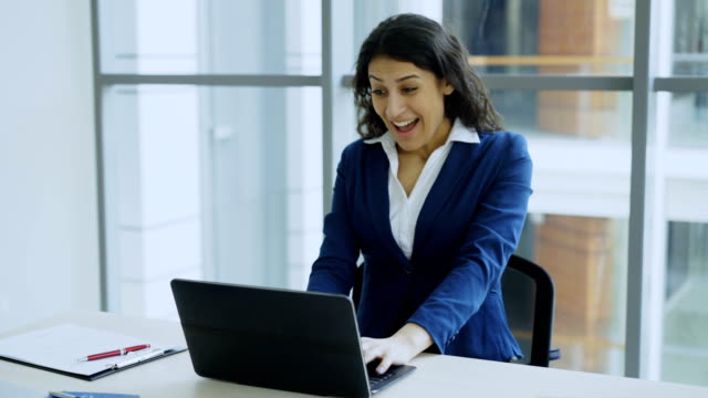 young businesswoman using laptop computer receiving good message and become very excited and happy sits in modern office - hindus filmów i materiałów b-roll