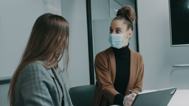 vídeos de stock e filmes b-roll de young businesswoman using laptop making business plan with colleagues with face masks during covid-19 pandemic in the office - envolvimento dos funcionários