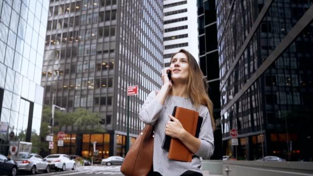 stockvideo's en b-roll-footage met jonge zakenvrouw lopen via het financiële district van new york, amerika en praten op mobiele telefoon. slow motion - business woman phone