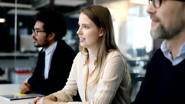 Young businesswoman with coworkers in meeting room