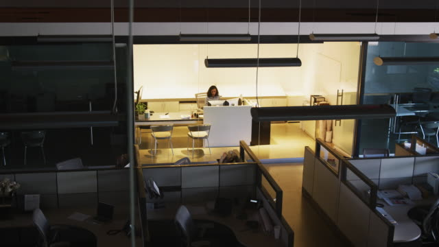 Young businesswoman working in empty office, elevated view Young businesswoman working in empty office, elevated view office cubicle stock videos & royalty-free footage