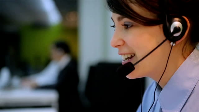 Young businesswoman working with a headset and accompanied by her team in call center. Young businesswoman working with a headset and accompanied by her team in call center. call centre videos stock videos & royalty-free footage