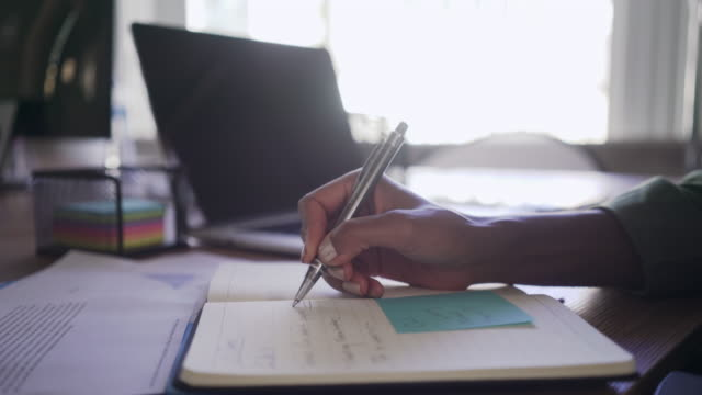 Young businesswoman writing on diary at office desk Close-up of a businesswoman making agenda on personal organizer at workplace personal organizer stock videos & royalty-free footage
