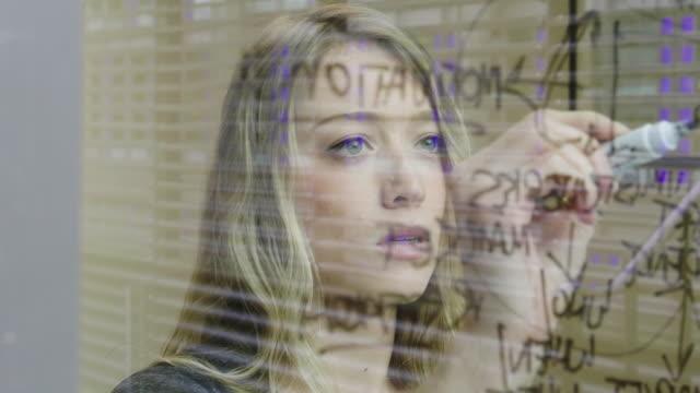 ts-junge geschäftsfrau schreiben mit einem stift auf glas - flussdiagramm stock-videos und b-roll-filmmaterial