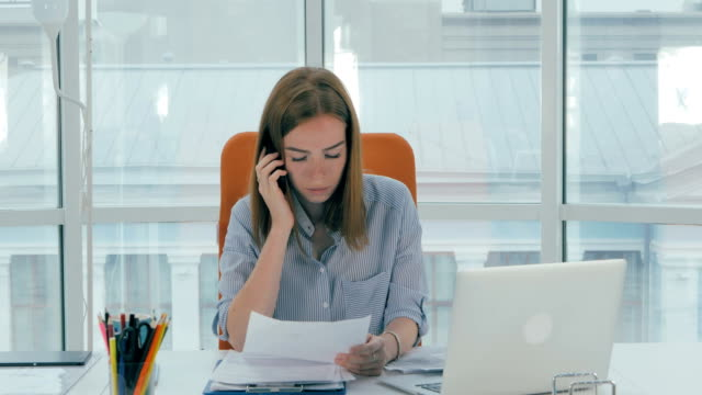 Young busy attractive business woman working in modern office. Timelapse video