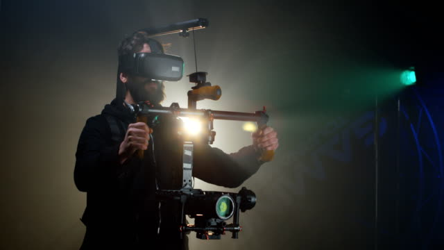 vídeos de stock e filmes b-roll de young cameraman shooting a scene - stabilized shot