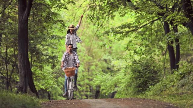 unga bekymmerslösa par ha kul medan ridning på cykel genom skogen. - ungt par bildbanksvideor och videomaterial från bakom kulisserna