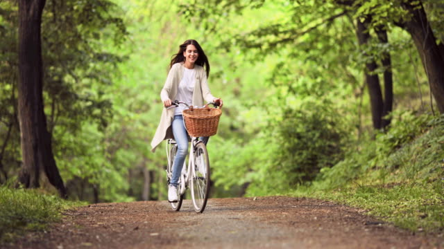 young carefree woman riding a bicycle through the park. - spring stock videos and b-roll footage