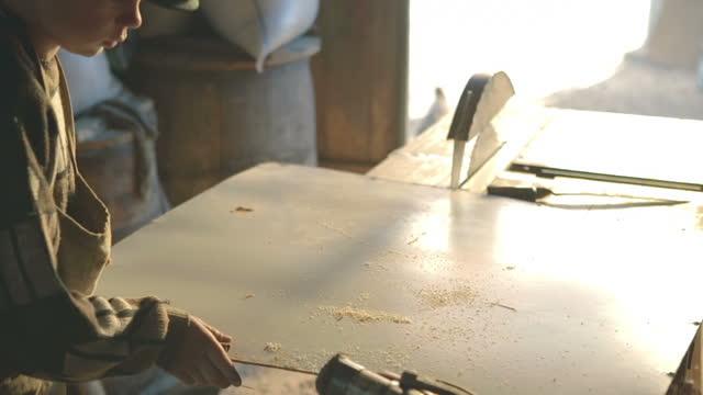 stockvideo's en b-roll-footage met jonge timmerman die een houten plank in workshop polijst - elektrisch gereedschap