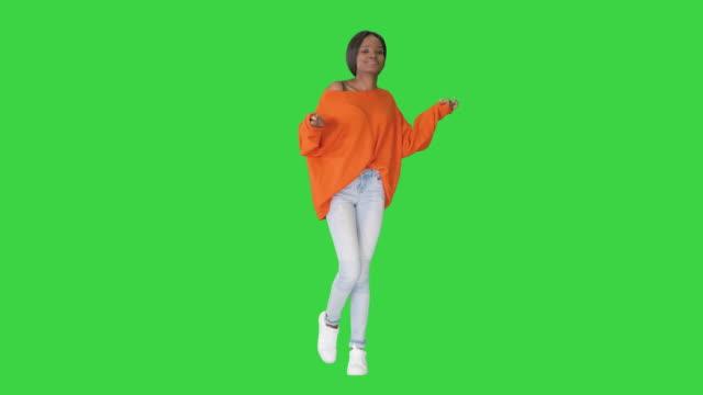 vídeos de stock, filmes e b-roll de jovem mulher africana casual dançando em uma tela verde, chroma key - artista