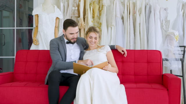 young casual couple looking the book sitting on sofa at wedding dress shop for choosing best dress wedding. - young couple wedding friends video stock e b–roll
