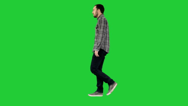 Young casual man walking on a Green Screen, Chroma Key