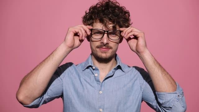 vídeos y material grabado en eventos de stock de joven hombre casual con camisa azul de pie y poner sus gafas en los ojos - moda preppy