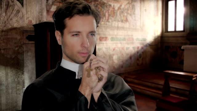 vídeos y material grabado en eventos de stock de joven contra un sacerdote decir oración - misa