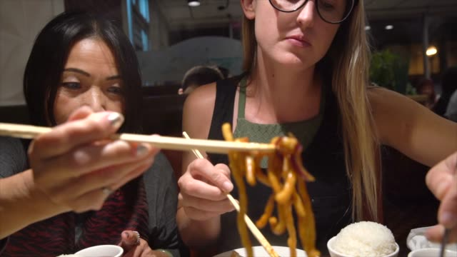 young caucasian and old asian woman eating noodles at restaurant video